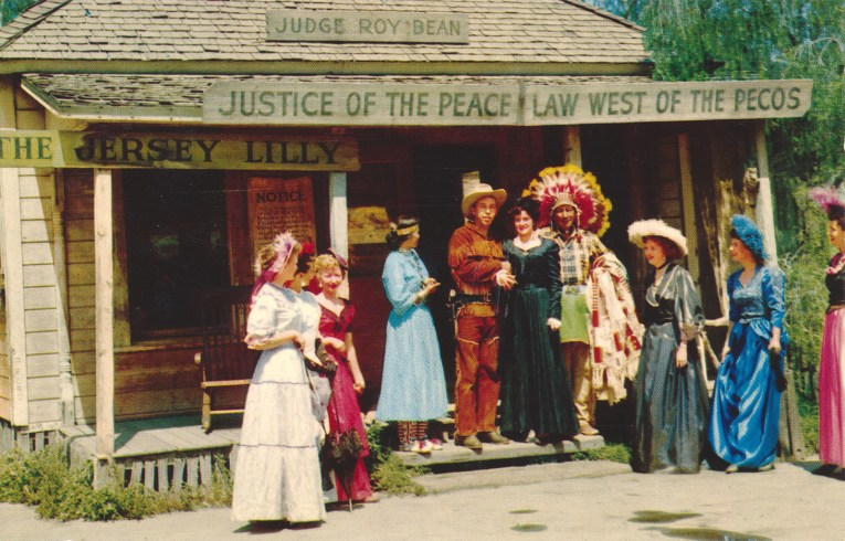 "Judge Roy Bean's, a small single story building with a sign reading ""Judge Roy Bean Justice of the Peace Law West of the Pecos"" A group of men and women in old western attire stand out front."