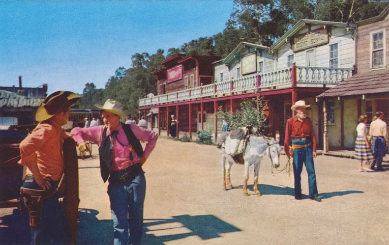 Men in old western attire stand along what is called School House Road, with old west buildings in the background.