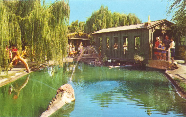 Jungle Island. A covered bridge is over a body of water, weird wood creatures are on the shore.