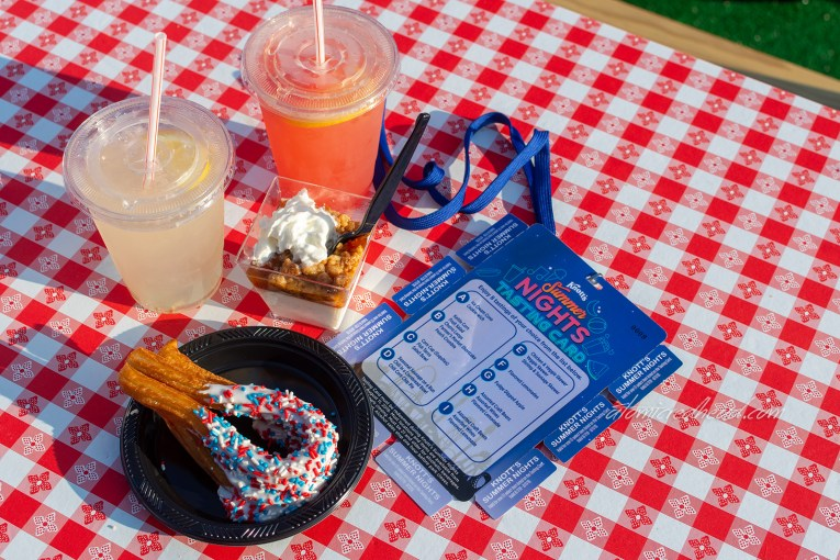 A cup of lemonade, a cup of watermelon lemonade, churros dipped in white frosting with red, white, and blue sprinkles, a small cup with peach cobbler in it, and the blue tasting card sit on a red and white gingham picnic table.