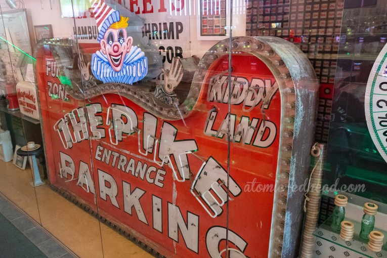 "A large vintage orange sign with white neon letters reading ""The Pike Entrance Parking Kiddy Land"" with a clown atop."