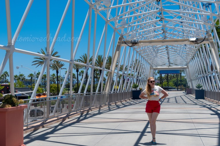 Myself standing on the Cyclone Racer Bridge, wearing a t-shirt with a female sunbather and the Cyclone Racer in the background, and red shorts.