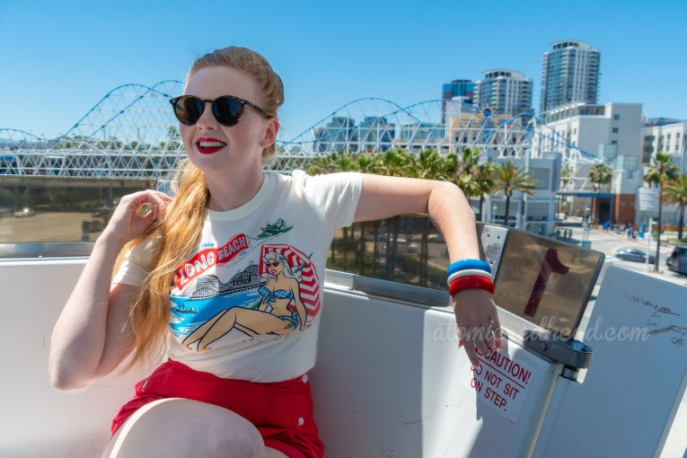 Myself sitting aboard the ferris wheel, wearing a t-shirt with a female sunbather and the Cyclone Racer in the background, and red shorts, the Cyclone Racer Bridge visible in the background.