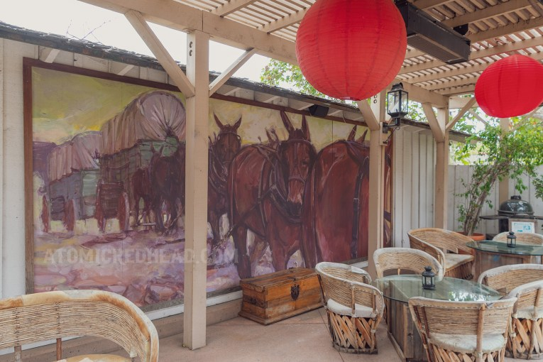 A mural of a covered wagon being pulled by horses on a wall of the outdoor courtyard.
