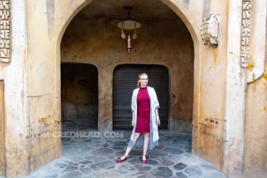 Myself standing in front of one of the doorways of Batuu, wearing a grey, lace duster, over a dark read dress, my hair in braids and pinned in the back.