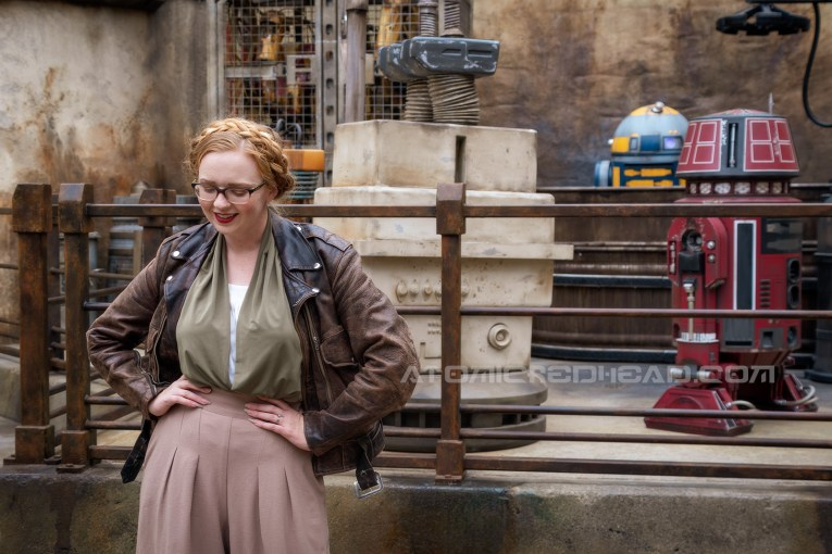 Myself standing in front of a raised platform with droids in various stages of being built, wearing a dark brown motorcycle jacket, a green and white blouse, and tan wide leg slacks.