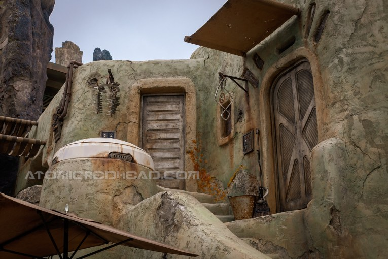 An almost adobe style home of Batuu, with a dusty seafoam color, wind chimes hanging from an awning.