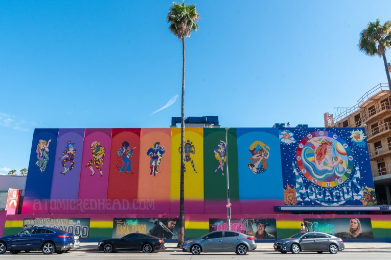 """A rainbow paint job covers the former Earl Carroll. Panels, each a different color, feature psychedelic characters, including dancers, musicians, acrobats, and jugglers. A massive painting of a nude man with long red hair pouring water from pitchers is painted on the right side, icons of astrology circle him. """"Aquarius"""" is painted below him."""
