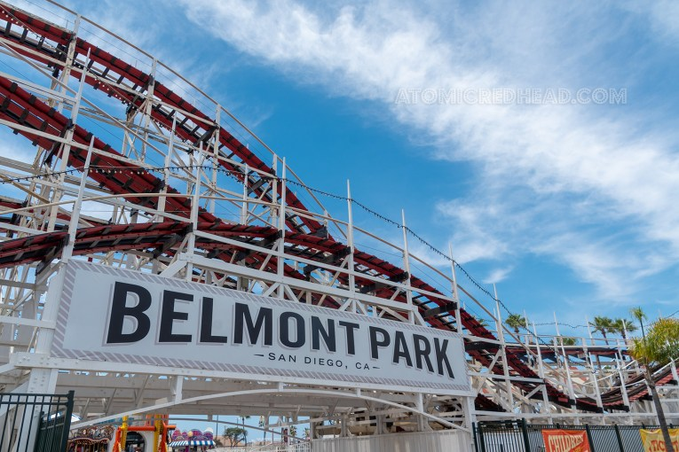 "A large wooden roller coaster painted white stretches toward a blue sky. A white sign with black letters reading ""Belmont Park"" is attached to the coaster."