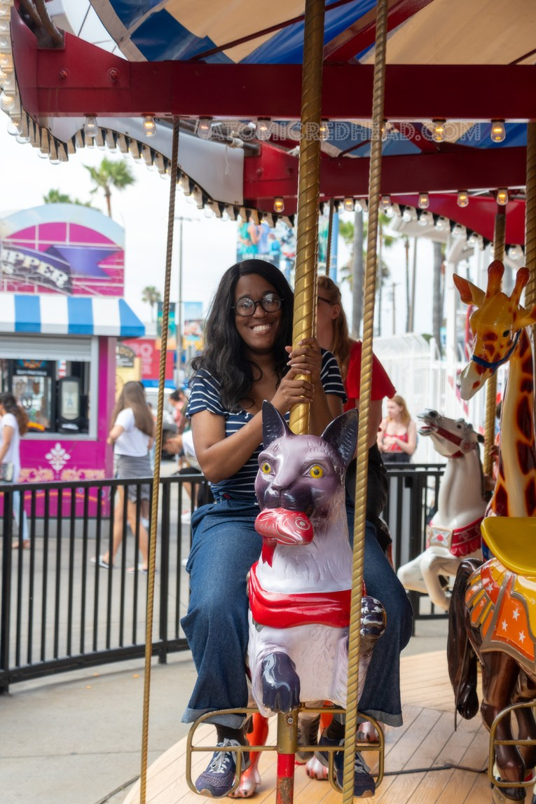 Carla rides a large siamese cat with a fish in its mouth on the carousel.