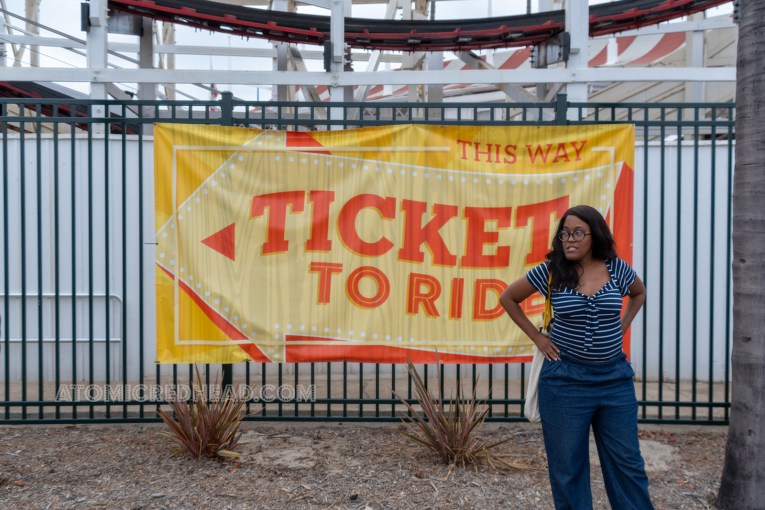 "Carla stands in front of a sign reading ""Ticket to Ride"" wearing a navy and white stripe shirt and jeans."