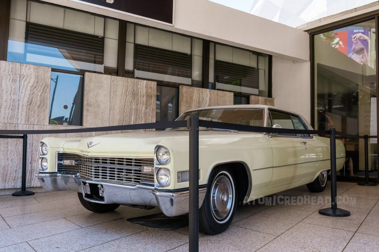 An off white Cadillac Coupe De Ville, which was used in the film, sits in front of the white marble box office.
