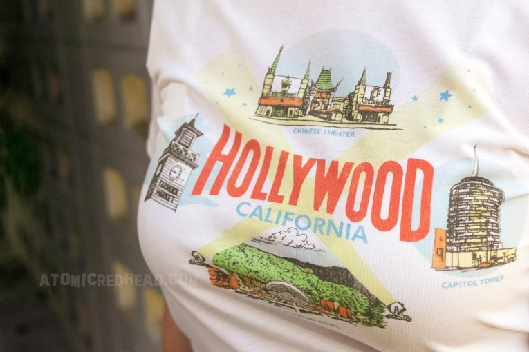 "Close-up of my shirt, which reads ""Hollywood"" in red letters and ""California"" in smaller blue letters. At the top is an illustration of Grauman's Chinese Theatre, on the left is an image of the clock tower from Farmer's Market, on the right an image of the Capitol Records building, and on the bottom the Hollywood Bowl."