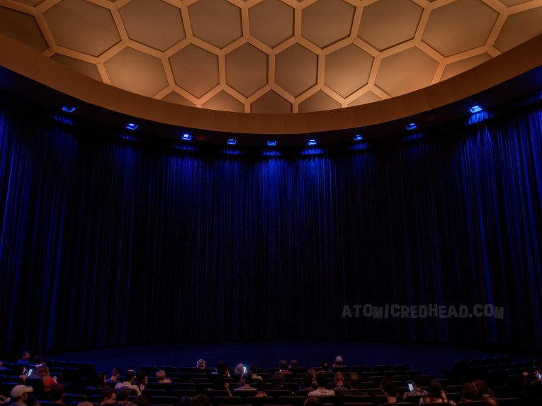 Inside the Theatre, a blue curtain hangs along the curved walls. The tiles that make up the structure are seen from within in their various shapes.