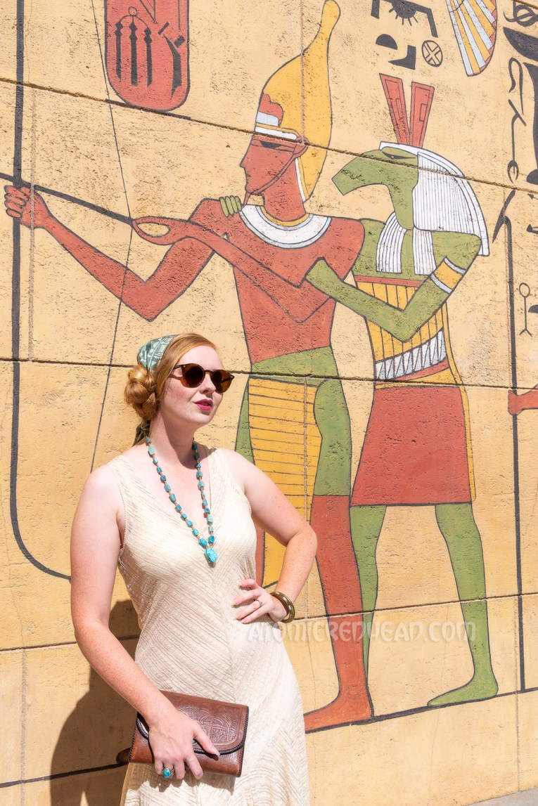Myself standing in front of a wall in the forecourt that is painted with images of Egyptian gods, kings and hieroglyphs, wearing a sleeveless cream lace dress, a blue scarf with white hieroglyphs, and a blue scarab necklace.