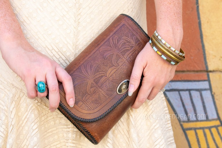 Close-up of my purse and jewelry. Purse is brown leather with an image of palm trees. Gold tone bracelets, on one wrist, a blue scarab ring on the other hang.