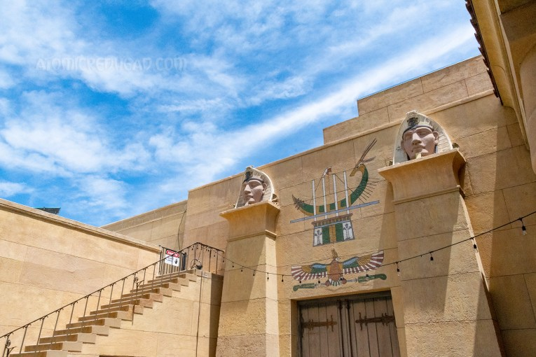A pair fo wooden doors sit between two pillars, above the doors is a mural of a hawk and a boat, atop the pillars are images of Egyptian pharaohs.