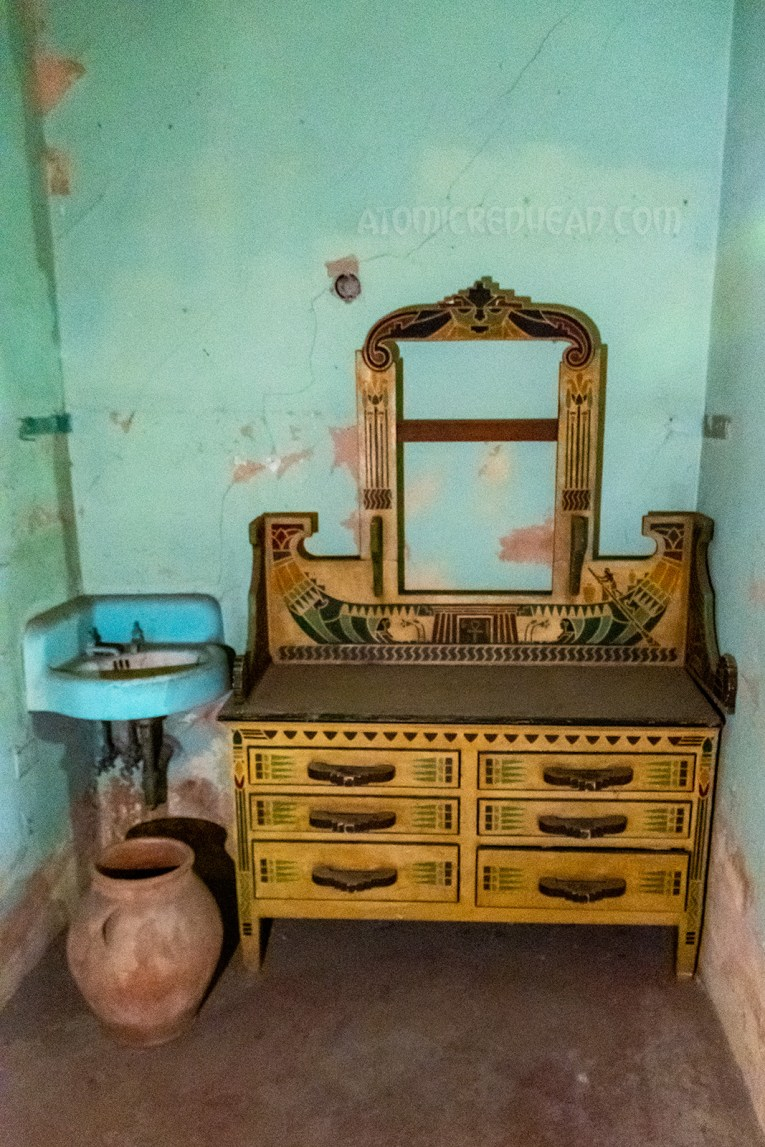 A yellow vanity is painted with an Egyptian motif. It sits against a blue wall with a small sink in the corner.
