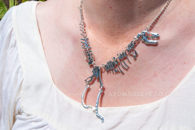 Close-up of my necklace, a silver T-Rex skeleton.