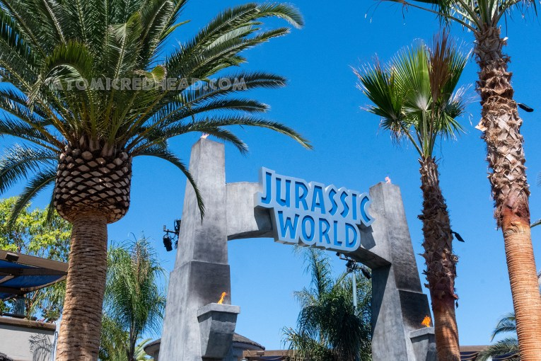 """The Jurassic World Archway to the ride, which is a grey stone arch with blue letters edged in grey reading """"Jurassic World"""""""