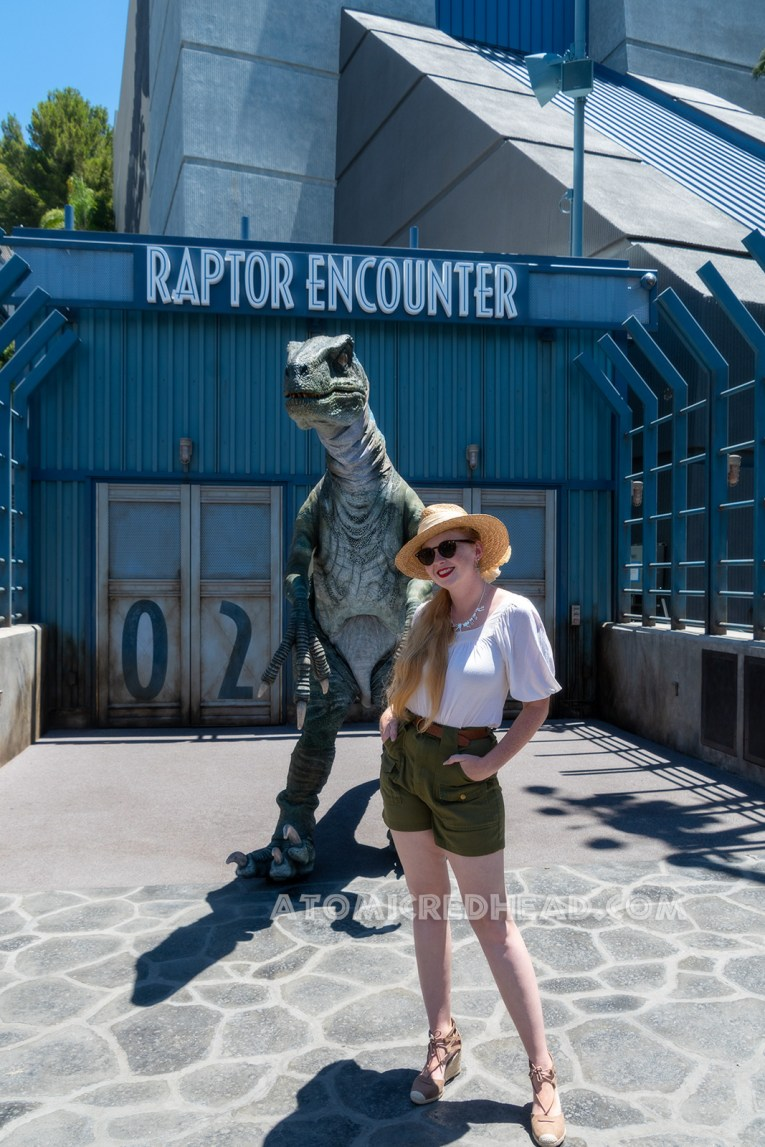 """The raptor known as """"Blue"""" for her blue stripe down her side stands outside the Jurassic World ride for Guests to take photos with, I stand in front of her, wearing a straw hat, white peasant top, and olive green shorts."""