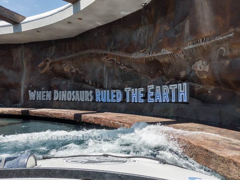 "Onboard grey rafts, Guests glide down an open corridor, where on one wall a massive Mosasaurus fossil sits in a wall, below text reads ""When dinosaurs ruled the earth"""
