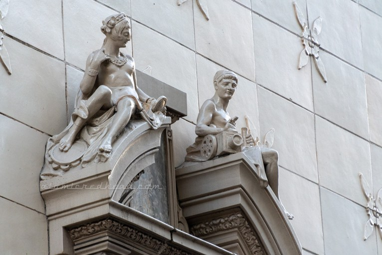 Two figures sit atop windows of a building. A topless female figure holds a hand mirror. A male figure sits near a camera and holds a megaphone.