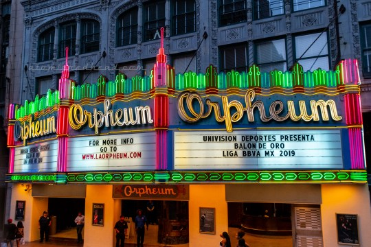 "The marquee for the Orpheum theatre, which reads ""Orpheum"" in yellow neon script, and lines of pink and green neon above."