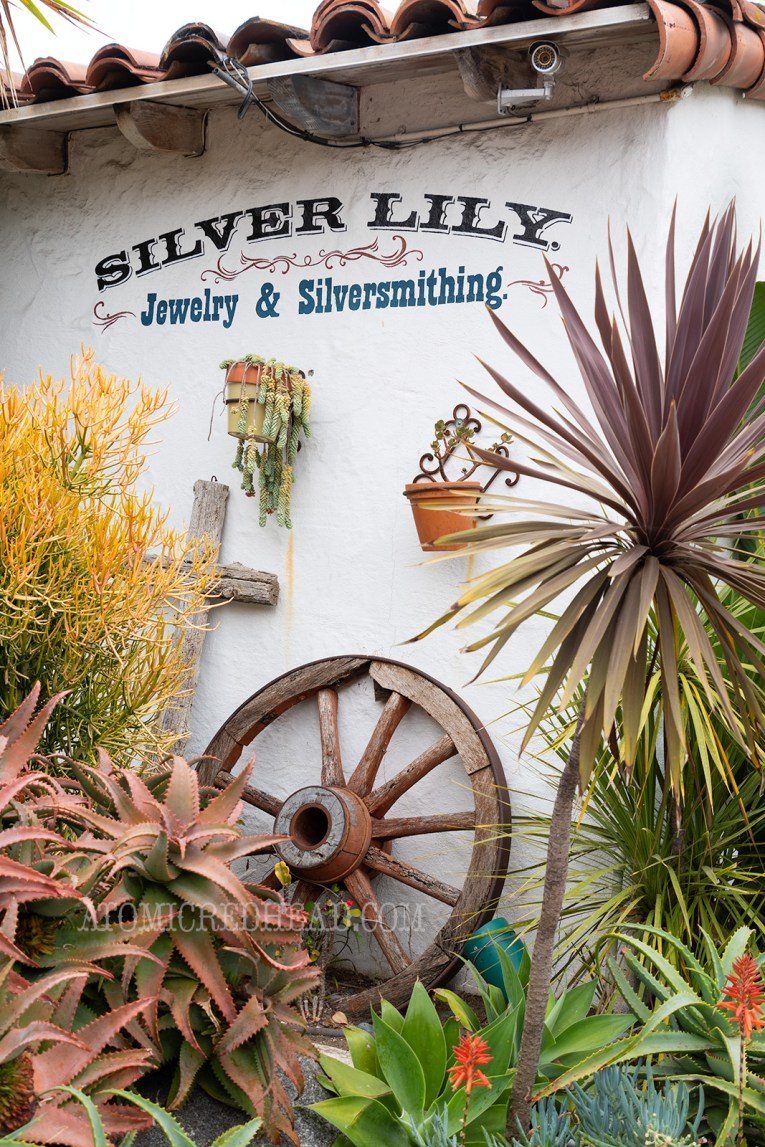 "A white adobe wall reads ""Silver Lily Jewelry & Silversmithing"" with succulents and cacti below, along with an old wagon wheel."