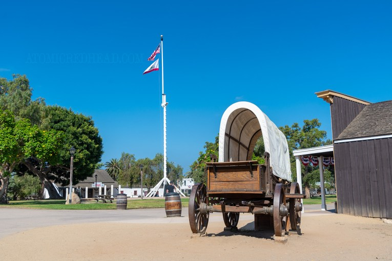 A covered wagon sits near the green lawn of the plaza with a tall flag pole features the American and California flags.