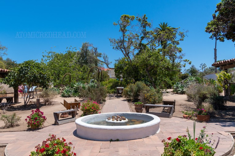 Courtyard of an adobe home, with a fountain and lush green plants beyond.