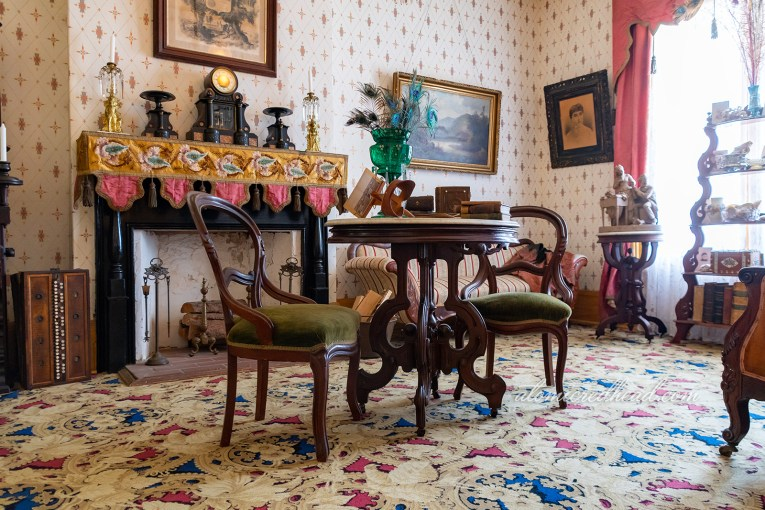 The parlor of the home, in front of the fireplace sits a small table and two chairs.
