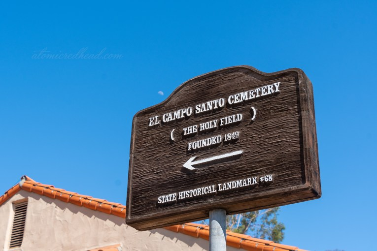 "A wooden sign reads ""El Campo Santo Cemetery (The Holy Field) Founded 1849 State Historical Landmark #68"""