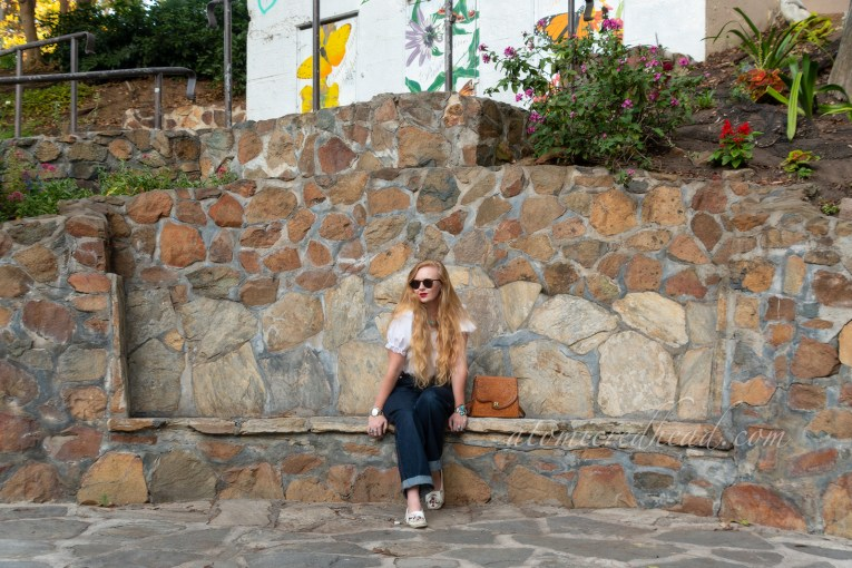 Myself sitting on a bench made into one of the rock walls, wearing a white peasant top and jeans.