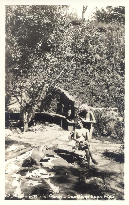 A black and white image of a woman brushing another woman's hair while seated. Both are nude. Rock work behind them forms short walls and a bench, the rest is various vegetation of trees and bushes.