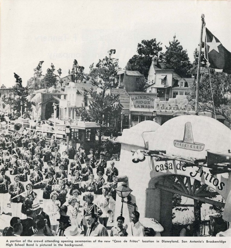 "A black and white photograph of the Casa De Fritos on the opening of its new location. A Mexican style building in the right foreground features a painted sombrero and script reading ""Casa de Fritos"" along the left is a large crowd of people. In the background are various western buildings. Caption at the bottom reads ""A portion of the crowd attending opening ceremonies of the new 'Casa de Fritos' location in Disneyland. San Antonio's Brackenridge High School Band is pictured in the background."""