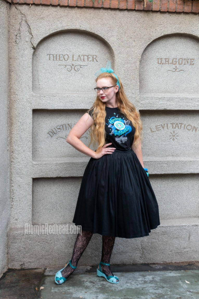 """Myself standing in front of a faux mausoleum at the Haunted Mansion, wearing a black t-shirt with Madam Leota (a medium with her head floating in a crystal ball) and music instruments floating about on it, reading """"Having a Ball"""" and a black full skirt."""