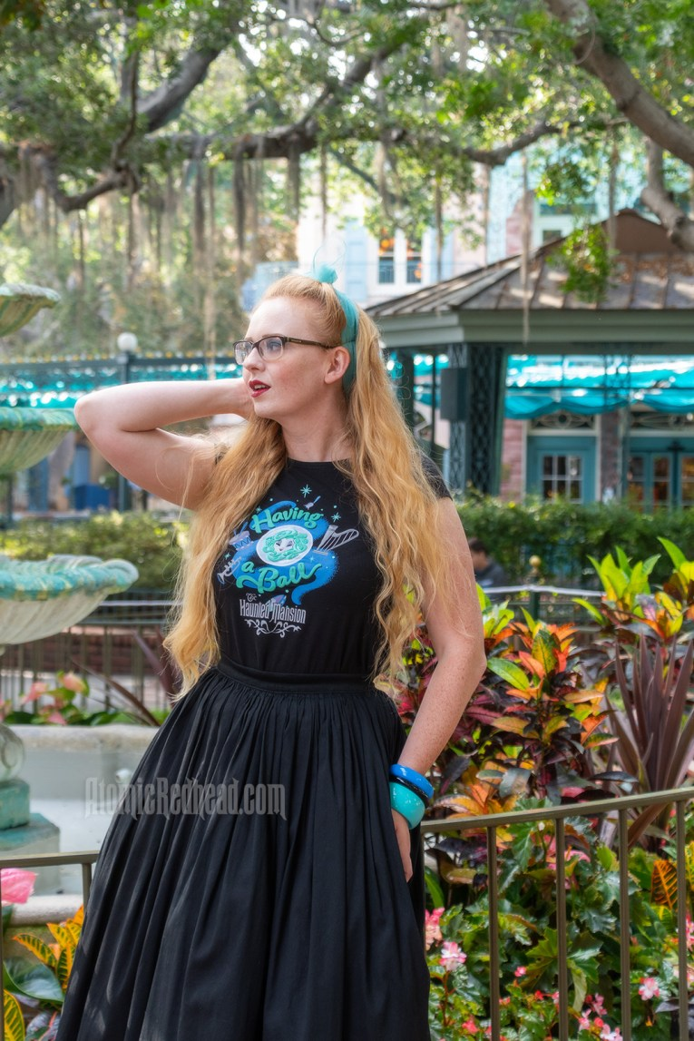 """Myself standing in front of a fountain surrounded by trees dripping in Spanish moss, wearing a black t-shirt with Madam Leota (a medium with her head floating in a crystal ball) and music instruments floating about on it, reading """"Having a Ball"""" and a black full skirt."""