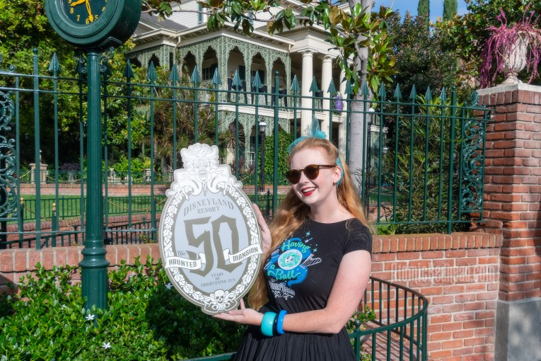 """Myself standing in front of the Haunted Mansion, Myself standing in front of a fountain surrounded by trees dripping in Spanish moss, wearing a black t-shirt with Madam Leota (a medium with her head floating in a crystal ball) and music instruments floating about on it, reading """"Having a Ball"""" and a black full skirt, holding a sign reading """"50 Years of Frightening Fun"""""""