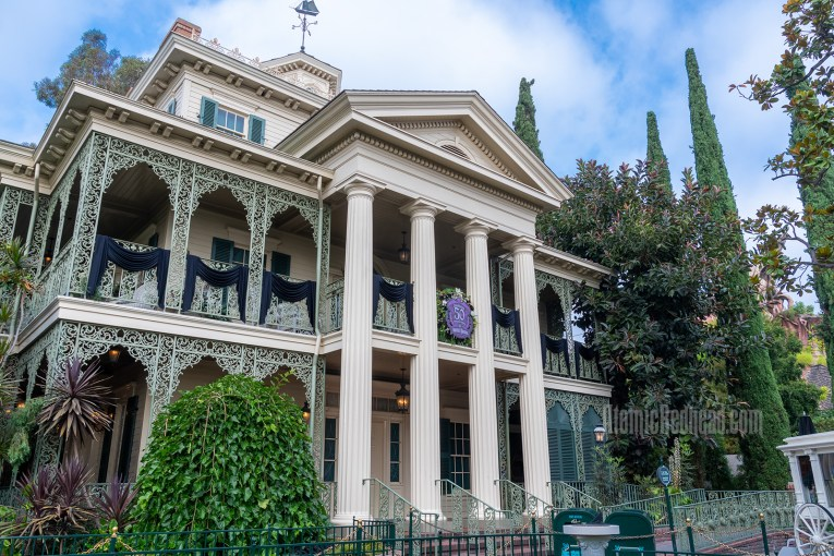 The Haunted Mansion, a stately two story Greek Revival, antebellum mansion with white pillars in center and curling green wrought iron around the side.