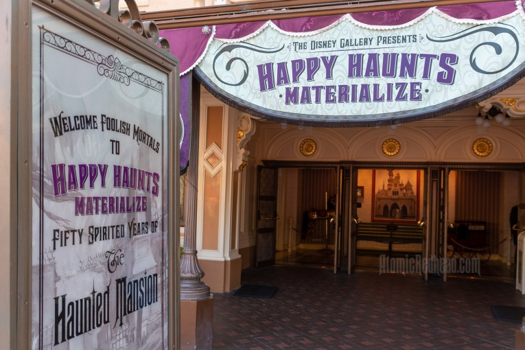 "A sign in the left foreground reads ""Welcome Foolish Mortals to the Happy Haunts Materialize Fifty Spirited Years of the Haunted Mansion"" in the background a banner reads ""The Disney Gallery Presents Happy Haunts Materialize"""