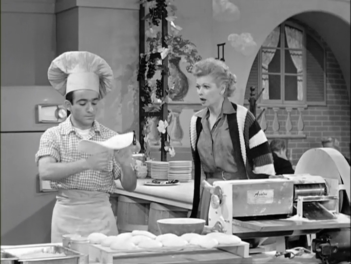 Screencap: A black and white image of Lucy, who looks in awe as a man in a large chef hat twirls pizza dough inside an Italian restaurant.