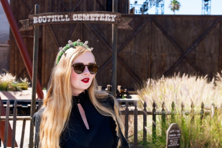 Myself, wearing a black long sleeve high collar blouse, and a long black skirt, holding a black coffin shaped purse, and a tiara made of small tombstones, standing in the Boot Hill cemetery, which features wooden tombstones.
