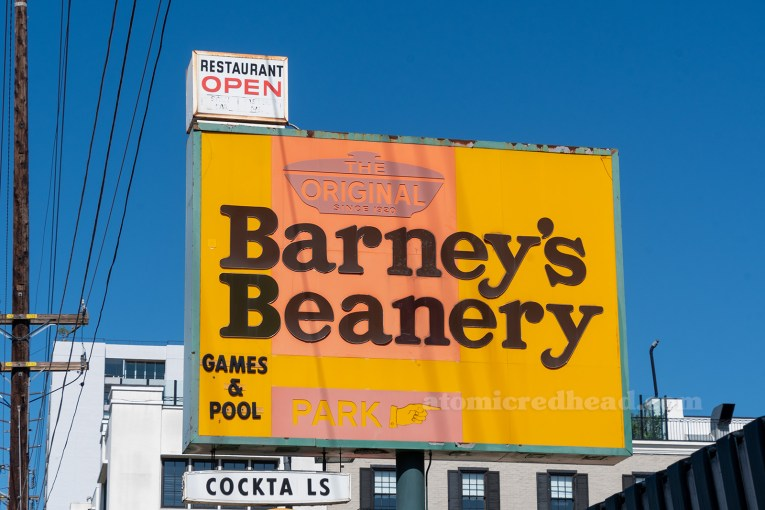"Close-up of the sign, a small white sign sits on top of a larger sign. The small sign reads ""Restaurant Open"" the larger sign reads ""The Original Barney's Beanery Games & Pool"" another smaller white sign reads ""Cocktails"""