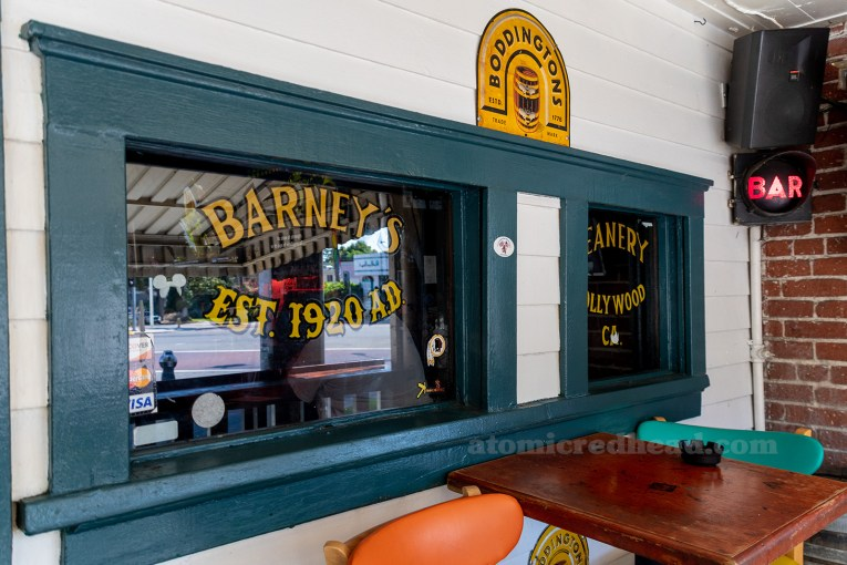 "The frame of a window is painted green, the rest of the building white, the text on the window reads ""Barney's Beanery Est. 1920 AD Hollywood California"""