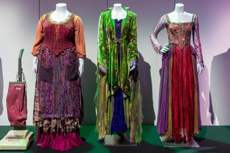 The costumes of the Sanderson sisters from the 90s film Hocus Pocus. Mary wears a red blouse under a red corset top, and purple apron like overskirt over a magenta skirt. Winfred wears a green cloak with a purple dress under. Sarah wears a purple fishnet top under a pink corset top, and a purple and red skirt.