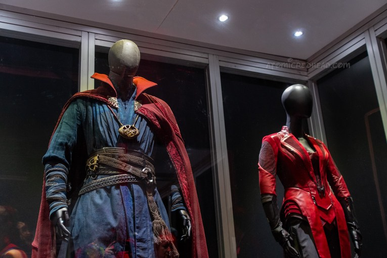 Dr. Strange and Scarlet Witch's costumes from Avengers. Dr. Strange wears a navy ensemble with multiple brown leather belts, and a red cape, his iconic eye shaped necklace hangs. Scarlet Witch wears a tight fitting red ensemble.