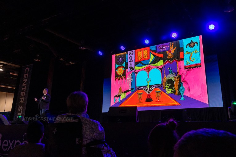 Christopher Merritt presents a panel on the Haunted Mansion and shows concept art for a fortune teller/medium type area, that is very colorful with banners and a crystal ball.