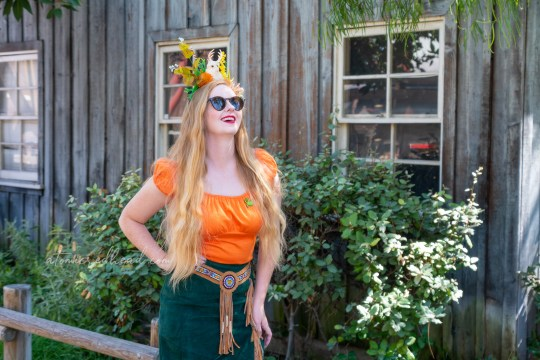 Myself standing in front of some western buildings wearing an orange peasant top and green skirt with tan fringe on the edge. Atop my head a crown made of succulents and a small jackalope.