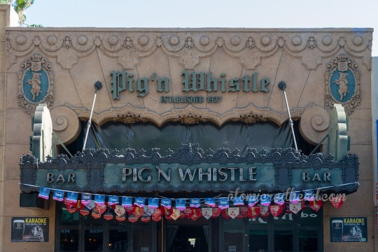 "Exterior of Pig 'n Whistle, in a gothic font ""Pig 'N Whistle"" is above a metal awning that reads ""Pig 'n Whistle"" in neon."